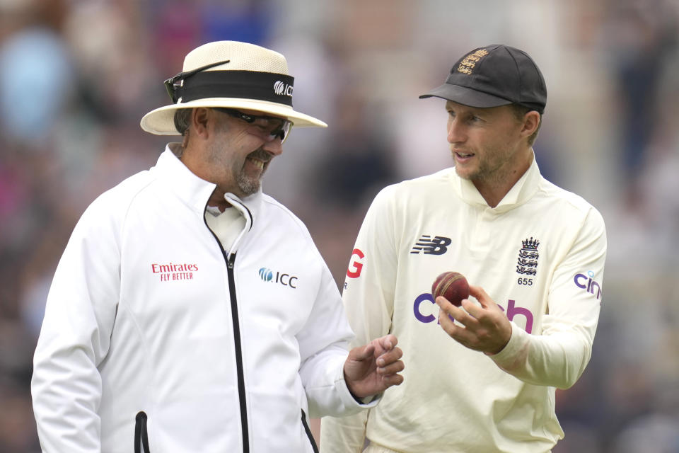 England's Joe Root and Umpire Richard Illingworth discuss the ball as they leave for tea on day three of the fourth Test match at The Oval cricket ground in London, Saturday, Sept. 4, 2021. (AP Photo/Kirsty Wigglesworth)