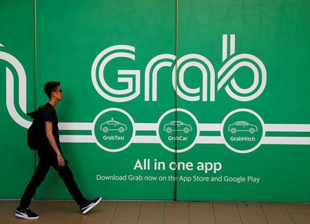FILE PHOTO: A man walks past a Grab office in Singapore March 26, 2018. REUTERS/Edgar Su/File Photo
