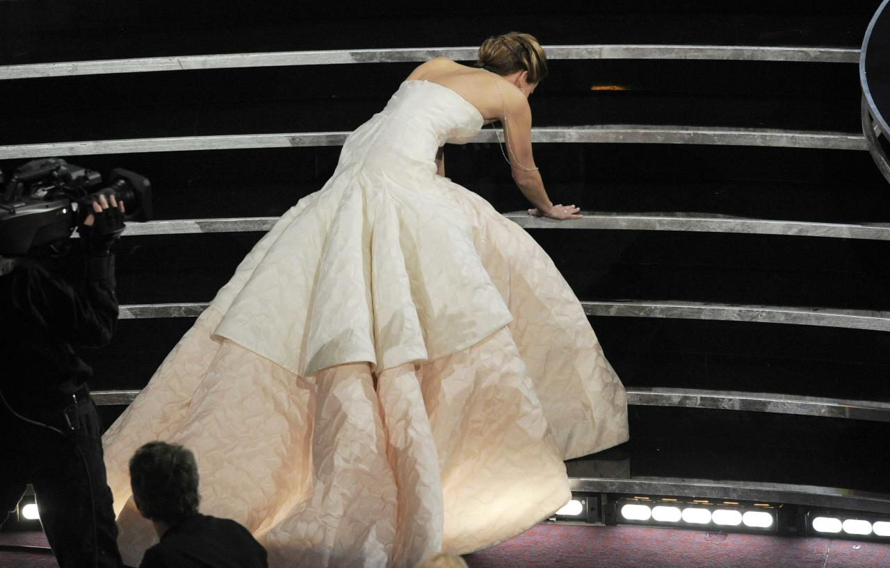 "Jennifer Lawrence stumbles as she walks on stage to accept the award for best actress in a leading role for ""Silver Linings Playbook"" during the Oscars at the Dolby Theatre on Sunday Feb. 24, 2013, in Los Angeles. (Photo by Chris Pizzello/Invision/AP)"