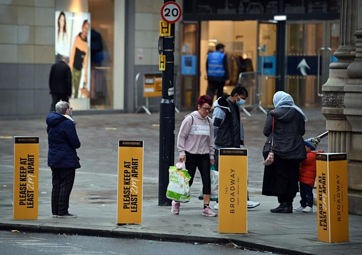 Shoppers walk past signs displaying COVID-19 guidelines, in the centre of Bradford, west Yorkshire on October 31, 2020, as the number of cases of the novel coronavirus COVID-19 rises. - British Prime Minister Boris Johnson is considering imposing a new lockdown across England within days following warnings his localised restrictions strategy has failed to curb soaring coronavirus rates, reports said Saturday. (Photo by Paul ELLIS / AFP) (Photo by PAUL ELLIS/AFP via Getty Images)