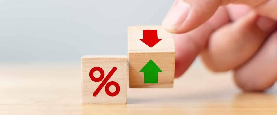 Interest rate concept for finance and mortgage rates.  Hand flip wooden cubes change arrow down up