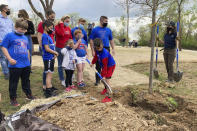 Educators and schoolchildren plant one of the trees at the dedication of Ohio's COVID-19 Pandemic Memorial Grove at Great Seal State Park near Chillicothe, Ohio, on April 30, 2021. A memorial grove to COVID-19 victims has been planted and governors and lawmakers elsewhere are pursuing similar permanent remembrances. (AP Photo/Julie Carr Smyth)