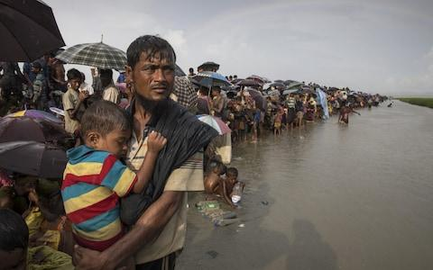 Rohingya refugees on river bank - Credit: Getty Images
