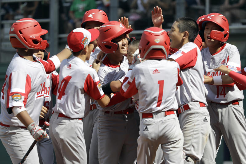 Japan's Yuto Misaki, center, celebrates his grand slam against Italy in the fifth inning of a baseball game at the Little League World Series tournament in South Williamsport, Pa., Friday, Aug. 16, 2019. (AP Photo/Tom E. Puskar)