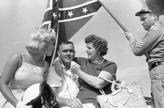 FILE - In this Sept. 3, 1962, file photo, a confederate flag is held behind Junior Johnson of Ronda, N.C., as he poses with his sister, right, and Ginger Pointevint, Miss Sun Fun U.S.A., left, in the winner's circle after the Southern 500 auto race at Darlington Speedway in Darlington, S.C. Bubba Wallace, the only African-American driver in the top tier of NASCAR, calls for a ban on the Confederate flag in the sport that is deeply rooted in the South. (AP Photo/Perry Aycock, File)