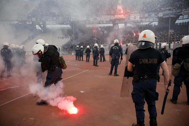 Soccer Football - Greek Cup Final - AEK Athens vs PAOK Salonika - Athens Olympic Stadium, Athens, Greece - May 12, 2018 Police look on while a flare is on the ground before the match REUTERS/Alkis Konstantinidis