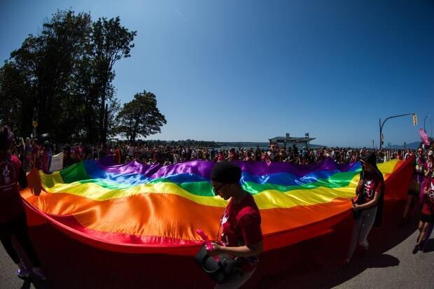 A large rainbow flag is carried by people marching in the Vancouver Pride Parade in Vancouver on Aug. 4, 2019. The Vancouver Pride Society is gearing up for its annual festivites on the B.C. Day long weekend and, with the spotlight on the local LGBTQ community, some members want to shed light on issues of racism they say are rampant. (Darryl Dyck/The Canadian Press - image credit)