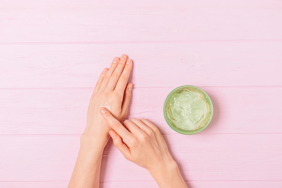 Female hands apply aloe gel on skin next to jar of cosmetic product on pink table, flat lay.