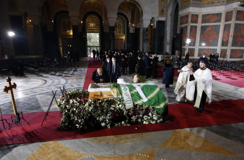 A man mourns by the coffin of Patriarch Irinej during the funeral procession at the St. Sava Temple in Belgrade, Serbia, Sunday, Nov. 22, 2020. The 90-year-old Irinej died early on Friday, nearly three weeks after he led the prayers at a funeral of another senior church cleric in neighboring Montenegro, who also died after testing positive for the virus. (AP Photo/Darko Vojinovic)