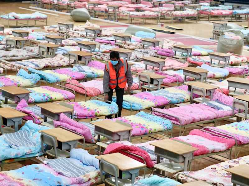 A worker sets up beds at the Hongshan Stadium to convert it into a makeshift hospital following an outbreak of the new coronavirus, in Wuhan, Hubei province, China February 4, 2020.