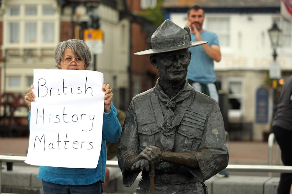 """A person with a sign protesting 'British History Matters' alongside the statue of Robert Baden-Powell on Poole Quay in Dorset. The statue is due to be removed and placed in """"safe storage"""" following concerns about his actions while in the military and """"Nazi sympathies"""". The action follows a raft of Black Lives Matter protests across the UK, sparked by the death of George Floyd, who was killed on May 25 while in police custody in the US city of Minneapolis."""