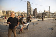 People carry a wounded after a massive explosion in Beirut, Lebanon, Tuesday, Aug. 4, 2020. Massive explosions rocked downtown Beirut on Tuesday, flattening much of the port, damaging buildings and blowing out windows and doors as a giant mushroom cloud rose above the capital. Witnesses saw many people injured by flying glass and debris. (AP Photo/Hassan Ammar)