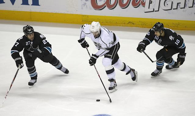 Los Angeles Kings left wing Dwight King (74) skates between San Jose Sharks center Andrew Desjardins (10) and defenseman Scott Hannan (27) during the third period of Game 4 of an NHL hockey first-round playoff series in San Jose, Calif., Saturday, April 26, 2014. Los Angeles won 3-0. (AP Photo/Tony Avelar)