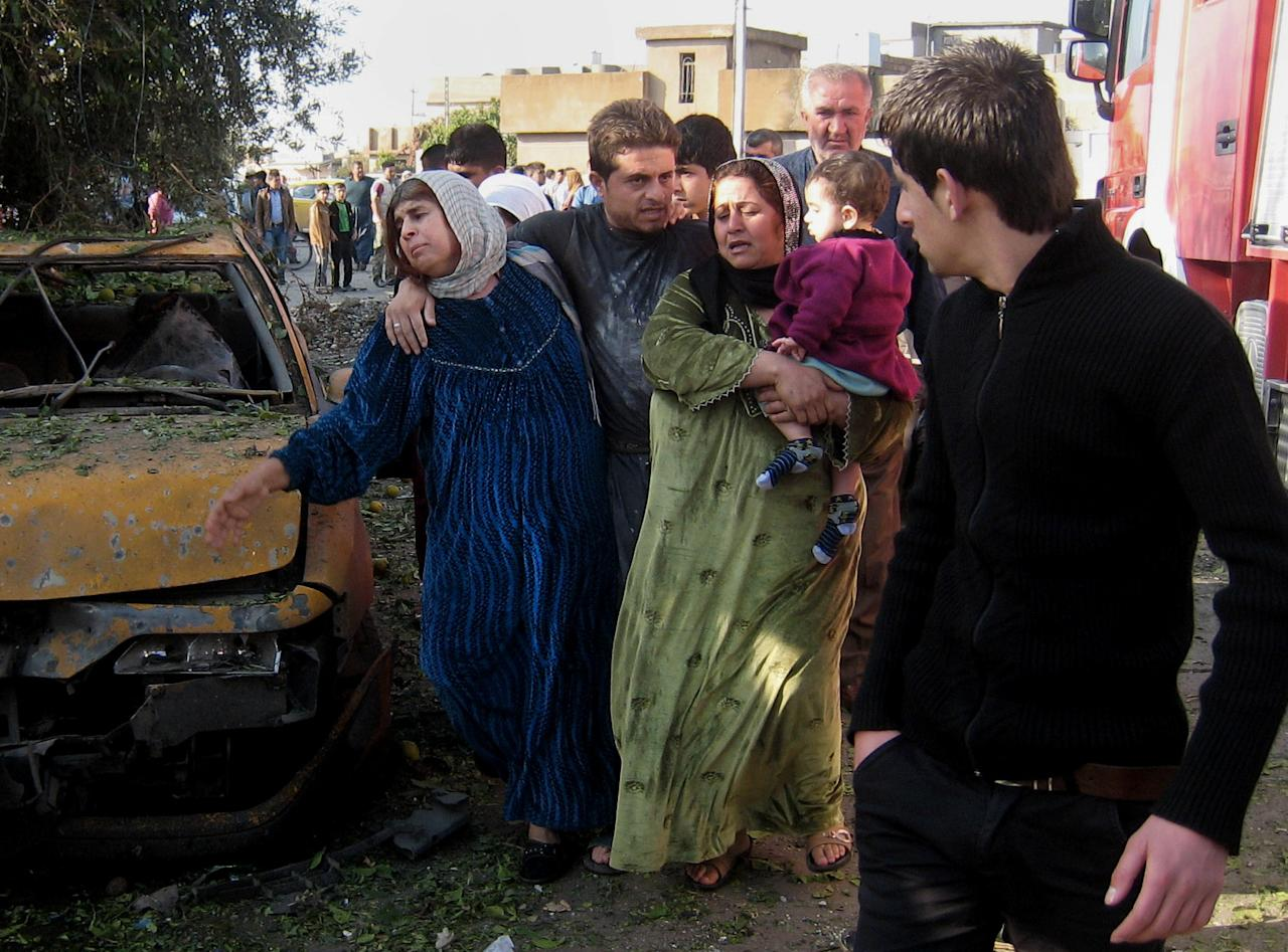 People react at the scene of a bomb attack in Kirkuk, 180 miles (290 kilometers) north of Baghdad, Iraq, Tuesday, Nov. 27, 2012. Three parked car bombs exploded Tuesday morning simultaneously in the city of Kirkuk, home to a combustible mix of Kurds, Sunni Arabs and Turkomen who all claim rights to the city, killing and wounding scores of people, police said. (AP Photo/Emad Matti)