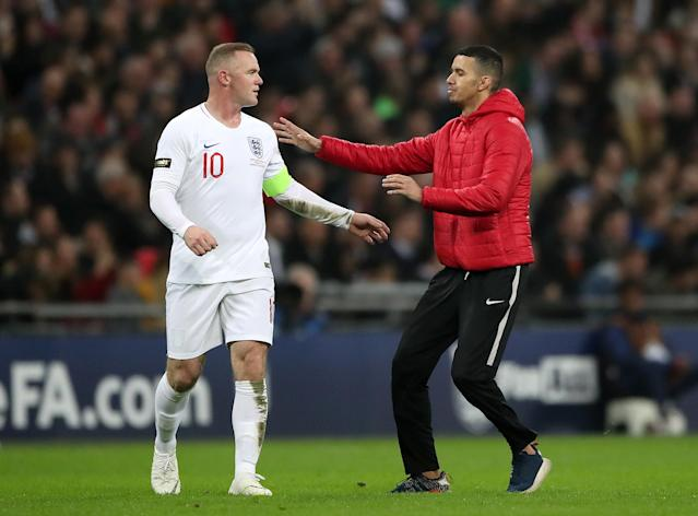 A pitch invader runs over to Rooney (Nick Potts/PA)