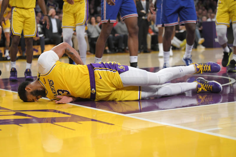 Los Angeles Lakers forward Anthony Davis winces as he hits the ground after falling while trying to defend against a shot by New York Knicks forward Julius Randle during the second half of an NBA basketball game Tuesday, Jan. 7, 2020, in Los Angeles. Davis left the game. The Lakers won 117-87. (AP Photo/Mark J. Terrill)