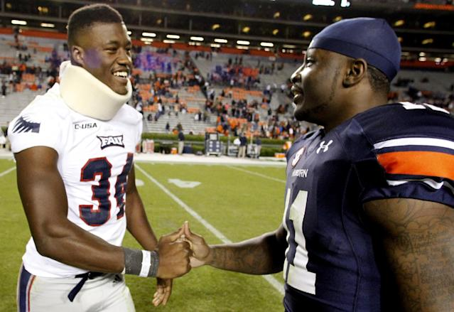 Florida Atlantic linebacker Freedom Whitfield (34) shakes hands with Auburn cornerback Chris Davis (11) after an NCAA college football game on Saturday, Oct. 26, 2013, in Auburn, Ala. Whitfield was injured tackling Davis during a punt return. (AP Photo/Butch Dill)
