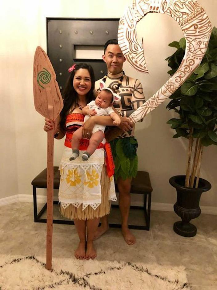 A couple dressed as Moana and Maui pose holding a paddle, sword, and a baby.