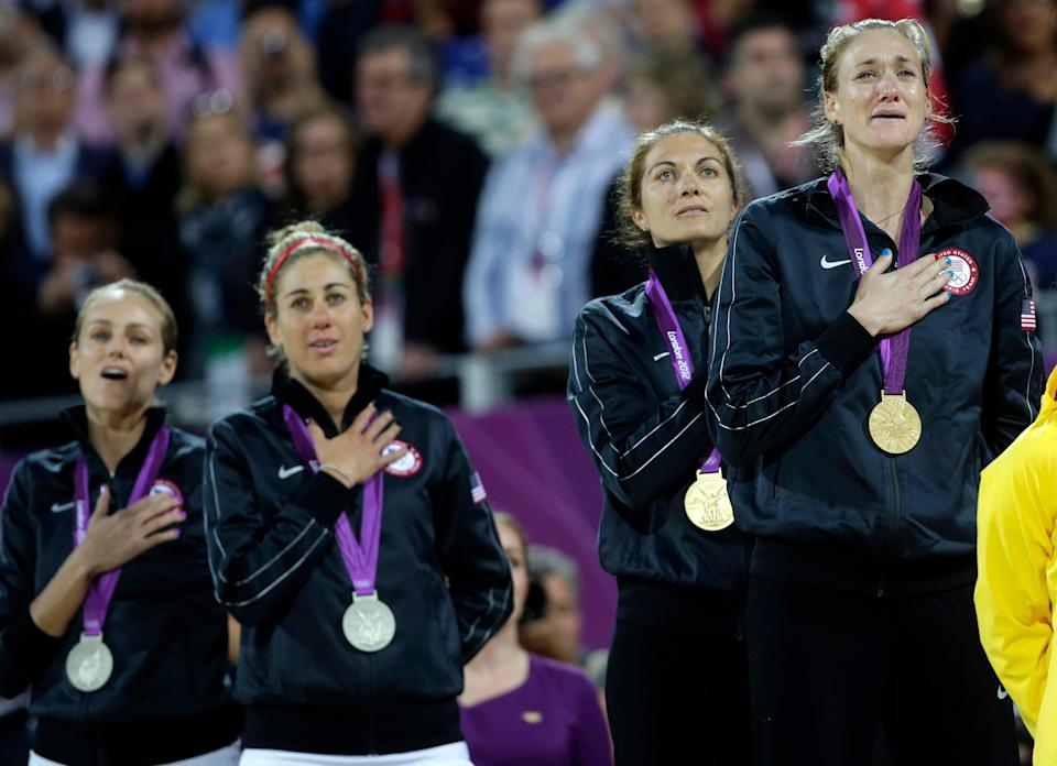 Women's beach volleyball silver Medalist Jennifer Kessy and April Ross, left, and gold medalist Missy May Treanor and Kerri Walsh Jennings, right, listen to the United States' national anthem the 2012 Summer Olympics in London. When longtime partner Misty May-Treanor retired after the London Games, Walsh Jennings looked across the net to grab Ross off the team they beat in the gold medal match.