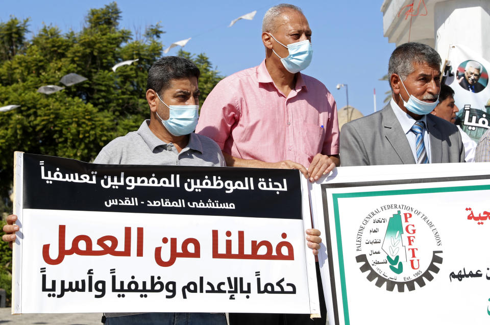 "Medical workers wear face masks and hold placards while staging a sit-in protest at the Unknown Soldier Square in Gaza City, Wednesday, Oct. 21, 2020. Arabic reads: ""Firing us is a death sentence on our profession and families."" Seven medical workers from the Gaza Strip said Wednesday an Israeli travel ban deprived them from getting to the east Jerusalem hospital where they worked for many years and the hospital eventually fired them. (AP Photo/Adel Hana)"