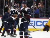 Colorado Avalanche right wing Joonas Donskoi, front, celebrates his hat trick as skaters pick up caps tossed onto the ice late in the third period of the team's NHL hockey game against the Nashville Predators on Thursday, Nov. 7, 2019, in Denver. Colorado won 9-4. (AP Photo/David Zalubowski)