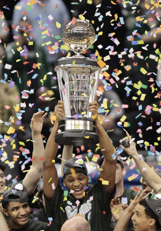 Michigan State forward Adreian Payne hoists the championship trophy after his team defeated Michigan 69-55 in an NCAA college basketball game in the championship of the Big Ten Conference tournament on Sunday, March 16, 2014, in Indianapolis. (AP Photo/AJ Mast)