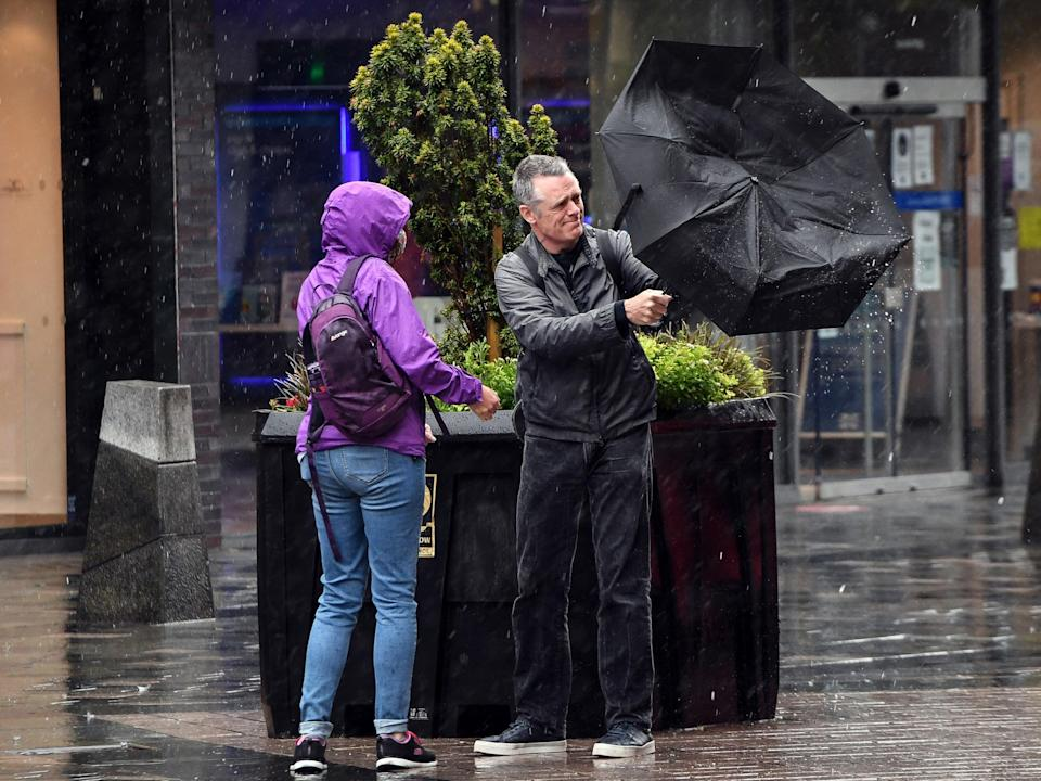 A couple battles with the elements in Glasgow city centre (AFP via Getty Images)