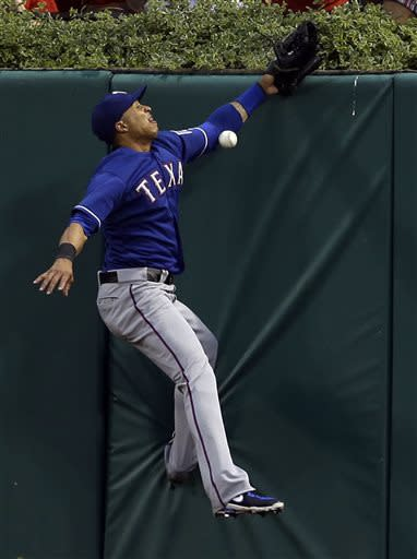 Texas Rangers center fielder Leonys Martin misses a ball hit for a triple by St. Louis Cardinals' David Freese during the second inning of a baseball game on Saturday, June 22, 2013, in St. Louis. (AP Photo/Jeff Roberson)