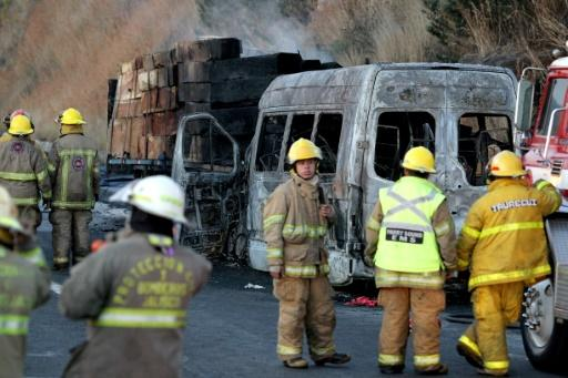 Firefighters and forensic medical personnel work at the scene of an accident between a tourist van and a cargo truck on the Lagos de Moreno highway in Zapotlanejo, Jalisco State, Mexico