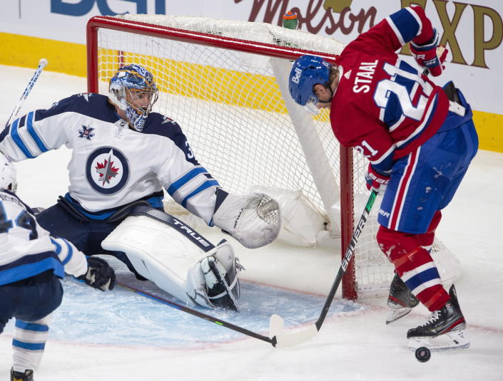 Winnipeg Jets goaltender Connor Hellebuyck (37) makes a save as Montreal Canadiens' Eric Stall looks for the rebound during the second period of an NHL hockey game, Thursday, April 8, 2021 in Montreal. (Ryan Remiorz/The Canadian Press via AP)