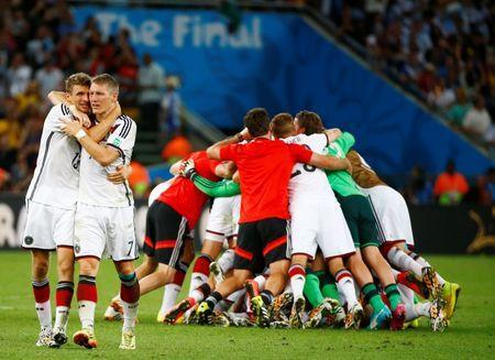 Germany's Thomas Mueller (L) and teammate Bastian Schweinsteiger embrace as they celebrate their win against Argentina during their 2014 World Cup final at the Maracana stadium in Rio de Janeiro July 13, 2014. REUTERS/Michael Dalder