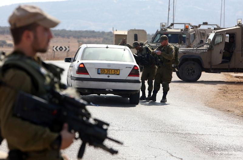 Israeli soldiers inspect a Palestinian car at a checkpoint close to the West Bank village of Beit Furik, east of Nablus, on October 2, 2015 (AFP Photo/Jaafar Ashtiyeh)