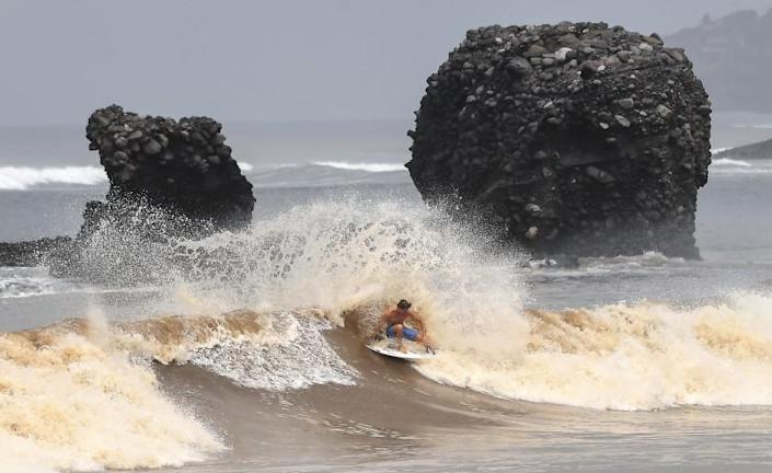 A surfer rides a wave in front of a volcanic rock resembling a pig, which gave the beach at El Tunco its name.