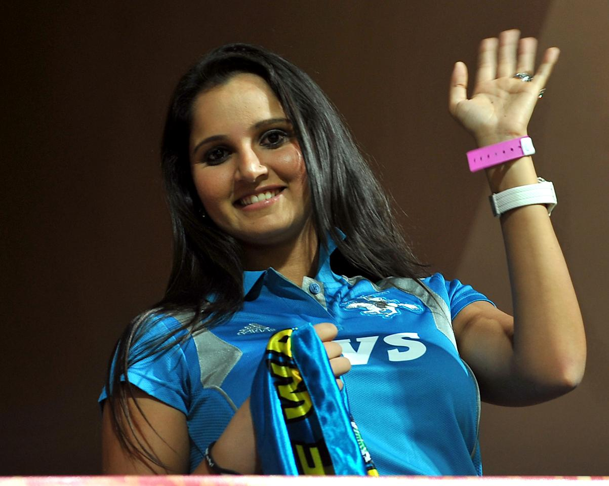 Indian tennis player Sania Mirza waves to photographers from the stands prior to the start of the IPL Twenty20 cricket match between Royal Challengers Bangalore and Pune Warriors at the M. Chinnaswamy Stadium in Bangalore on April 17, 2012.   RESTRICTED TO EDITORIAL USE. MOBILE USE WITHIN NEWS PACKAGE.   AFP PHOTO/Manjunath KIRAN (Photo credit should read Manjunath Kiran/AFP/Getty Images)