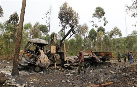 Congolese FARDC soldiers assess remains of a shelled truck used by M23 rebels outside Goma