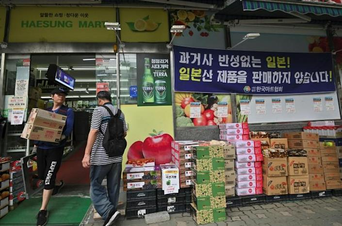 A blue banner (top R) outside a grocery shop in Seoul reads 'Japan - a country that does not regret its past. We do not sell Japanese products here' (AFP Photo/Jung Yeon-je)