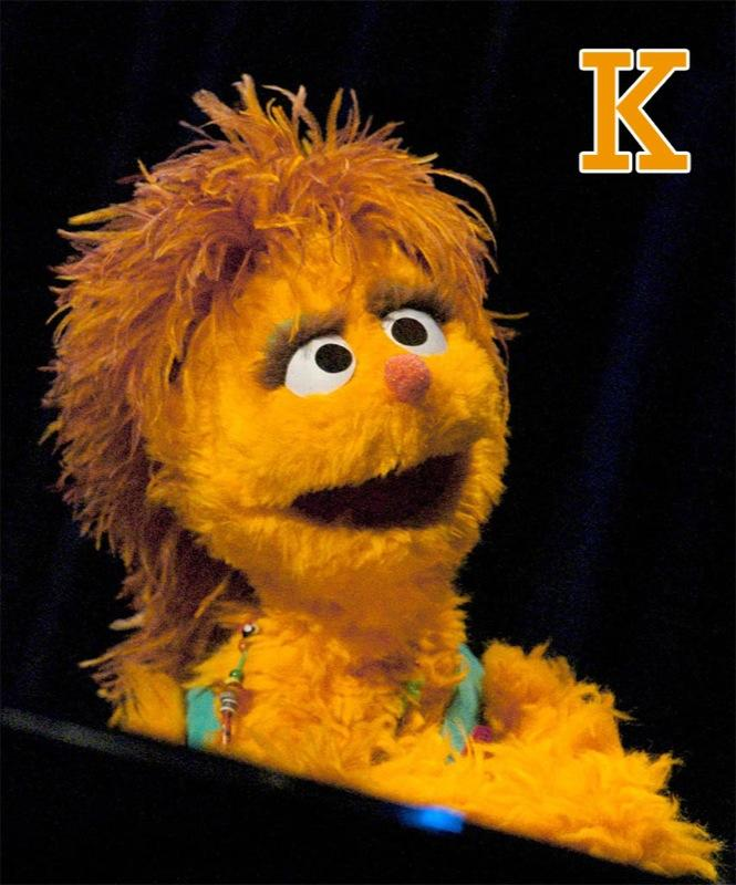"K is for Kami: Kami is an orange-furred HIV positive Muppet who originated on the South African version of <a href=""/sesame-street/show/33526"">""Sesame Street,""</a> called ""Takalani Sesame."" A shy Muppet, she's been made the ""Champion of Children"" by UNICEF. Kami, who was an orphan, speaks to kids around the world in her role. <a href=""http://www.zap2it.com/"" rel=""nofollow"">Source: Zap2it</a>"