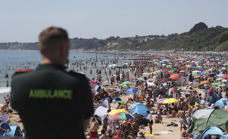 A member of the Ambulance service looks out at people crowded on the beach in Bournemouth, England, Thursday June 25, 2020, as coronavirus lockdown restrictions have been relaxed. According to weather forecasters Thursday could be the UK's hottest day of the year, so far, with scorching temperatures forecast to rise even further. (Andrew Matthews/PA via AP)