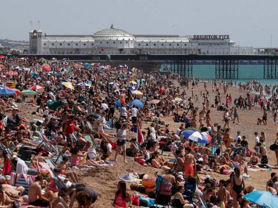 Beachgoers enjoy the sunshine and sea on what is now Britain's hottest day of the year so far, in Brighton (AP)
