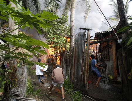Residents attempt to extinguish the flames from burning houses, caused by a firefight between government soldiers and Muslim rebels from the Moro National Liberation Front (MNLF), in a residential district in Zamboanga city in southern Philippines September 12, 2013.REUTERS/Erik De Castro