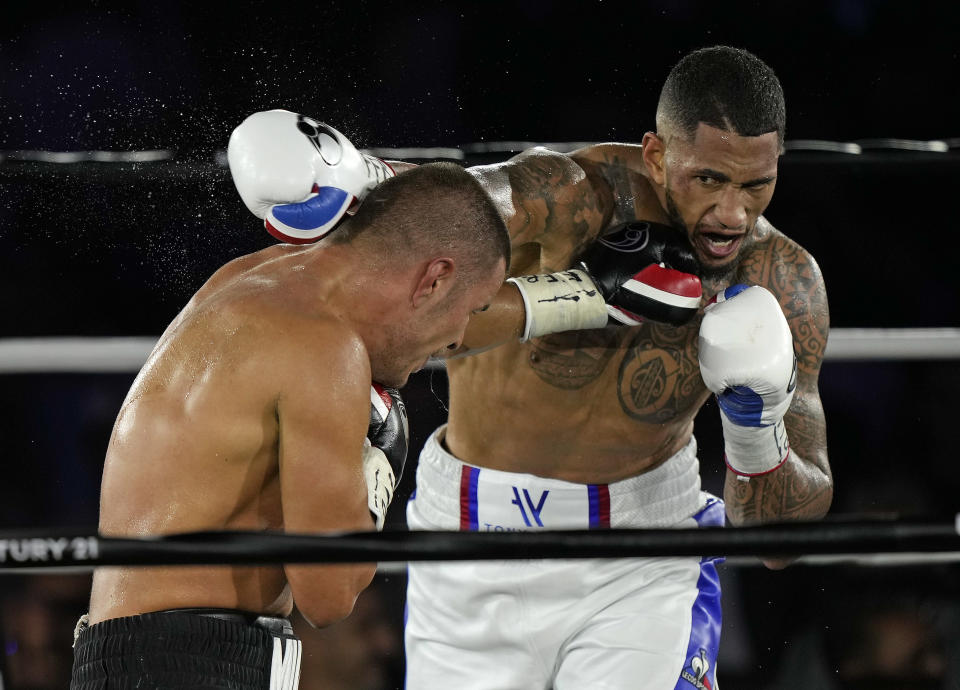 Tony Yoka of France, right, exchanges blows with Croatia's Petar Milas during their heavyweight boxing fight on the central court Philippe Chatrier at the Roland Garros tennis stadium, in Paris, Friday, Sept. 10, 2021. (AP Photo/Francois Mori)