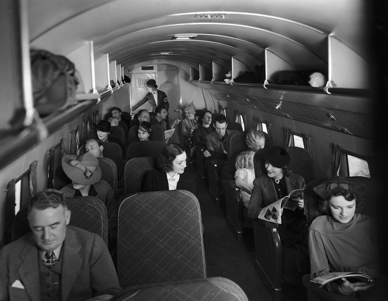 Passengers sitting in their seats inside the cabin of a 21-passenger airplane making daily trips between New York City and Chicago circa 1935.