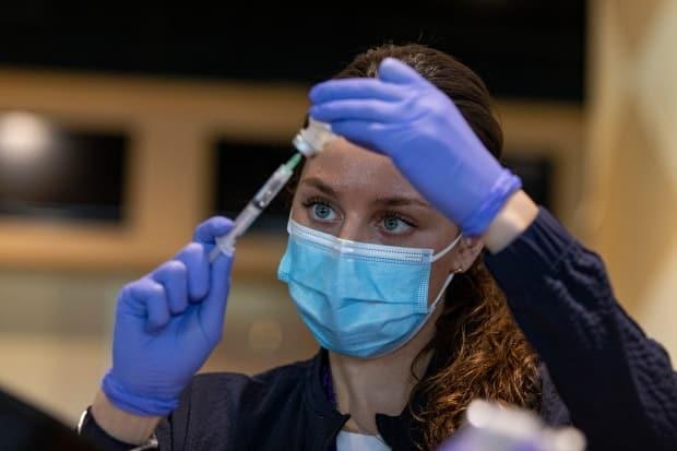 Registered nurse Sarah Moslehi prepares a dose of the Pfizer-BioNTech COVID-19 vaccine at a temporary clinic at the Woodbine racetrack and casino, in northeast Toronto, on May 5, 2021. (Evan Mitsui/CBC - image credit)