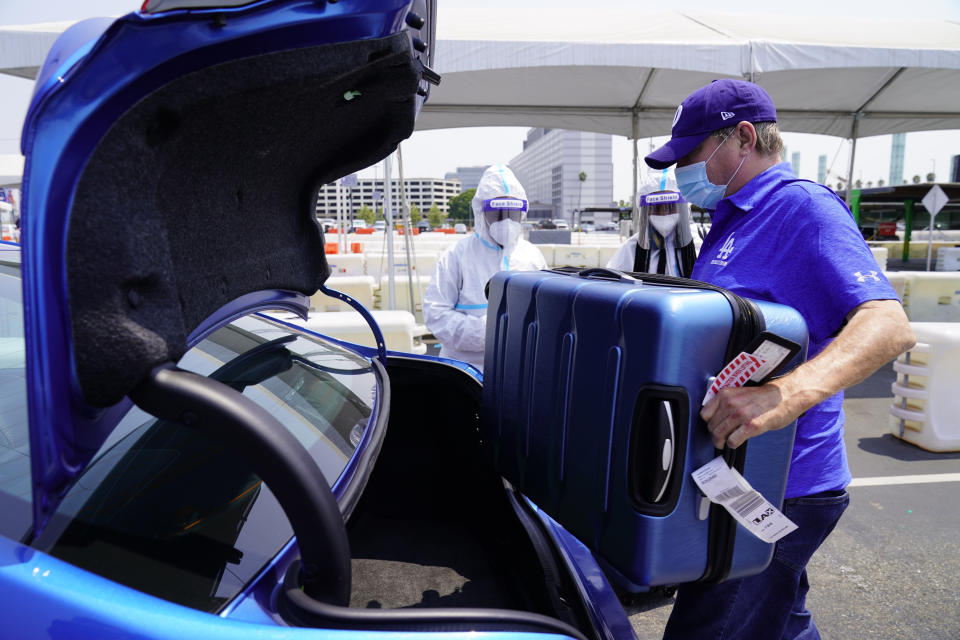 FILE - In this Aug. 20, 2020, file photo, Uber driver Ralph, only first name given, loads luggage from travelers arriving from New York City at Los Angeles International Airport's LAX-it pick up terminal. A judge has struck down California's ballot measure that exempted Uber and other companies from a state law requiring their drivers to be classified as employees eligible for benefits and job protections, Friday, Aug. 20, 2021. (AP Photo/Damian Dovarganes, File)