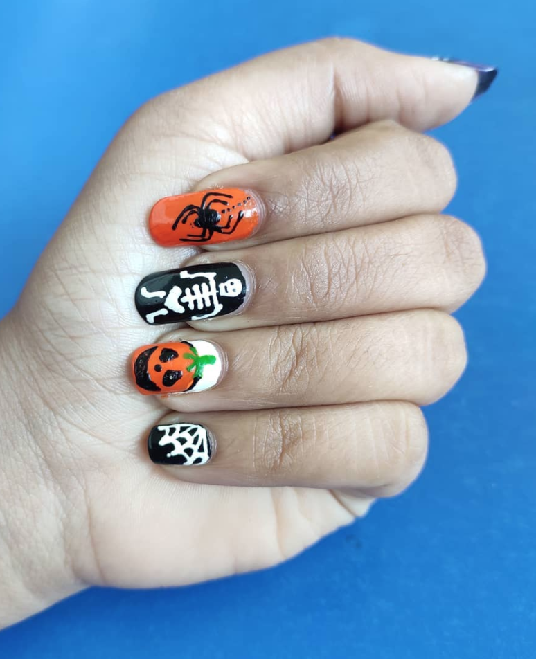 """<p>Can't decide on pumpkins, spiderwebs, or skeletons? The good news is that you can have them all on your nails, as demonstrated by <a href=""""https://www.instagram.com/nailed.__.it/"""" rel=""""nofollow noopener"""" target=""""_blank"""" data-ylk=""""slk:freehand artist Kalyani K. Patil"""" class=""""link rapid-noclick-resp"""">freehand artist Kalyani K. Patil</a>. To paint these on your own fingers, you'll need a couple of thin nail brushes.</p><p><a class=""""link rapid-noclick-resp"""" href=""""https://go.redirectingat.com?id=74968X1596630&url=https%3A%2F%2Fwww.ulta.com%2Fnail-art-tool-kit%3FproductId%3DxlsImpprod5190147&sref=https%3A%2F%2Fwww.oprahmag.com%2Fbeauty%2Fskin-makeup%2Fg33239588%2Fhalloween-nail-ideas%2F"""" rel=""""nofollow noopener"""" target=""""_blank"""" data-ylk=""""slk:SHOP NAIL TOOL KIT"""">SHOP NAIL TOOL KIT</a></p>"""