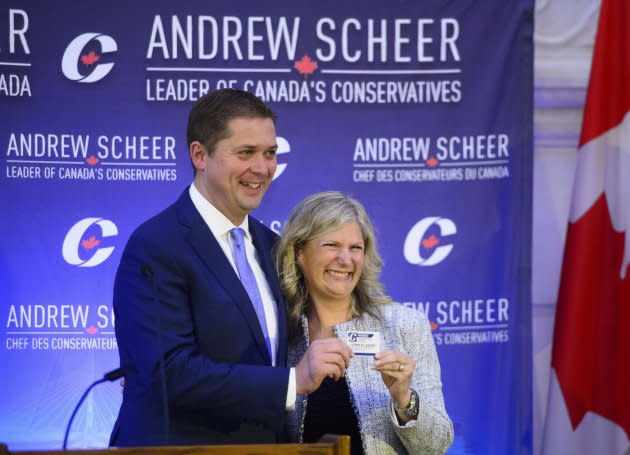 New Conservative MP Leona Alleslev is presented with a party card by Conservative Leader Andrew Scheer as she is welcomed during the caucus meeting on Parliament Hill in Ottawa on Sept. 19, 2018.