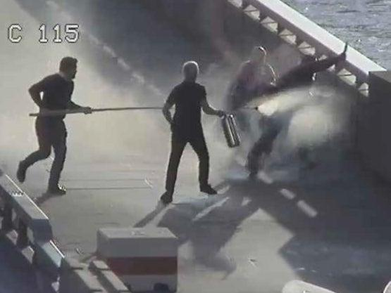 A still of CCTV footage showing John Crilly and Steven Gallant fighting Usman Khan on London Bridge, using a narwhal tusk and fire extinguisher (Met Police)