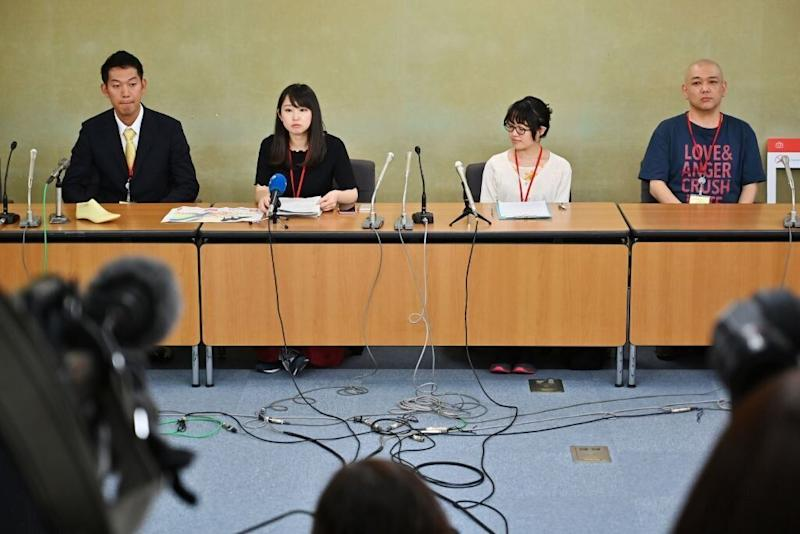 Yumi Ishikawa (second from left), leader and founder of the KuToo movement, is flanked by supporters as she delivers a speech during a press conference in Tokyo on June 3, 2019. [Photo: Getty]