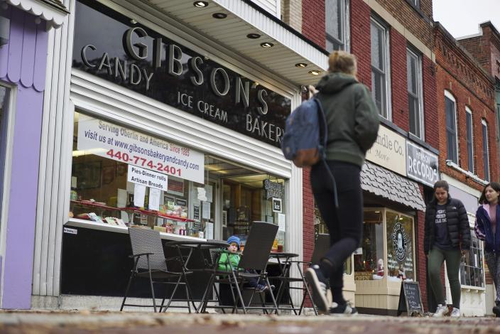 FILE - In this Nov. 22, 2017 file photo, pedestrians pass the storefront of Gibson's Food Mart & Bakery in Oberlin, Ohio. A jury has awarded $11 million to a father and son who claimed Ohio's Oberlin College and an administrator hurt their business and libeled them during a dispute that triggered protests and allegations of racism following a shoplifting incident. (AP Photo/Dake Kang, File)