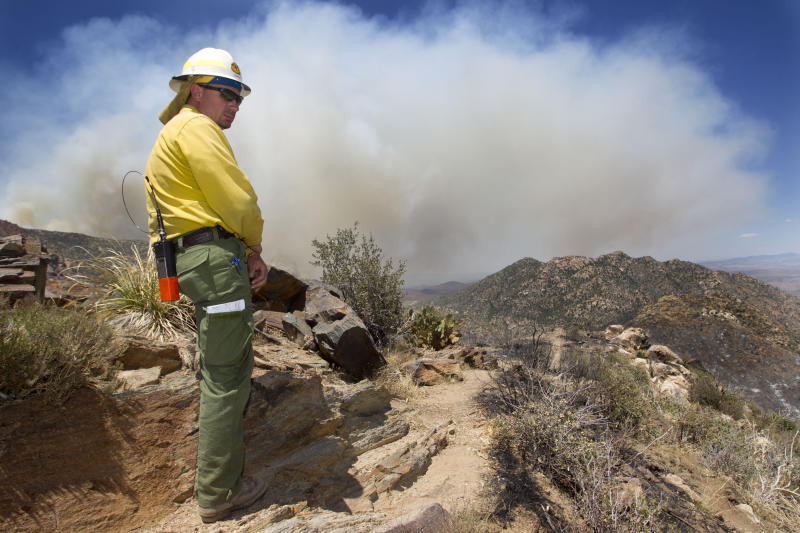 Todd Lerke with the U.S. Forest Service looks out on a ridge as he works against the wildfire as it burns in the Bradshaw Mountains in the Prescott National Forest, Ariz. Wednesday, May 16, 2012. (AP Photo/The Arizona Republic, David Wallace) MARICOPA COUNTY OUT; MAGS OUT; NO SALES